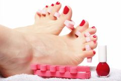 Foot pedicure applying red toenails on white Royalty Free Stock Photography