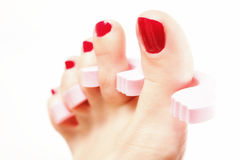 Foot pedicure applying red toenails on white Royalty Free Stock Photo