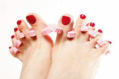 Foot pedicure applying red toenails on white Royalty Free Stock Photos