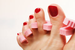 Foot pedicure applying red toenails on white Stock Image