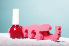 Foot pedicure red nail polish and toe separators Stock Images
