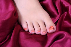Foot on piece of luxurious satin Royalty Free Stock Photography