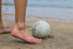 Foot playing football. Close-up of male foot playing football on a beach Royalty Free Stock Image