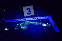 Foot print of criminal visible in UV light Stock Photos