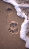 A foot print going to be covered by water Stock Photography
