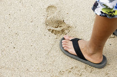 Foot print. Young boy standing on beaching with foot print in the sand Royalty Free Stock Images
