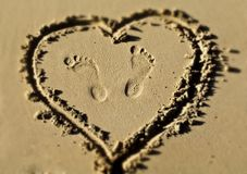 Foot prints inside a sandy heart Stock Photography