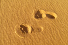 Foot prints on sand. Foot print on sand beach near the sea. Beautiful drawings on the yellow smooth sand. Leisure on the beach, romantic love Royalty Free Stock Photography