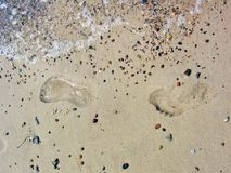 Foot prints with water, sand and stones Royalty Free Stock Images