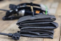 Foot pump and bicycle tube on a wooden workbench. Accessories fo. R bicycle and car tires repair. Dark background Stock Photography