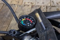 Foot pump and bicycle tube on a wooden workbench. Accessories fo. R bicycle and car tires repair. Dark background Royalty Free Stock Images