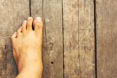 Foot rests on the old wooden floor. Background Stock Images