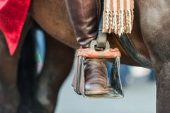 The foot of a rider on the stirrup of a horse stock photo