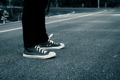 Foot on road backpacking travel. Royalty Free Stock Photo