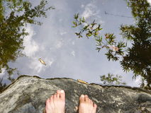 Foot on the rock and reflection of the wood Stock Photography
