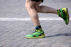 Foot running distance athlete on the stone pavement Stock Photos