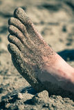 Foot in sand Stock Images
