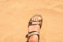 Foot in sandal on sand Royalty Free Stock Photography