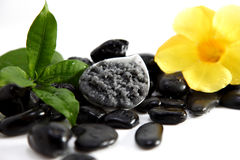 Foot Scrub. Black Organic Foot Scrub isolated on white with flowers and stones Stock Photo