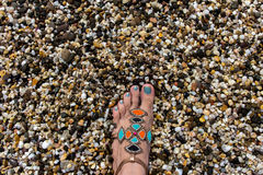 Foot on the sea stones. Different colors sea stones texture Royalty Free Stock Image