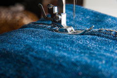 Foot of Sewing Machine on Jeans Stock Photo