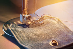 Foot of sewing machine on jeans fabric toned, warm light. Foot of sewing machine on a denim pocket illuminated by warm light toned, closeup Royalty Free Stock Image