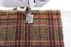 Foot of sewing machine on woolen textile Stock Photo