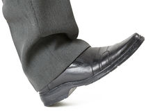 Foot in a shoe ready to crush Royalty Free Stock Image