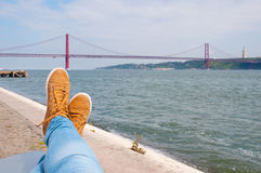 Foot an shoes. Resting near the water. Lisbon red bridge view at the background Royalty Free Stock Photos