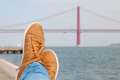 Foot an shoes. Resting near the water. Lisbon red bridge view at the background Stock Images