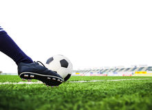 Foot shooting soccer ball on field Stock Image