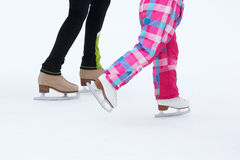 Foot skating little girls and women on an ice rink Royalty Free Stock Image
