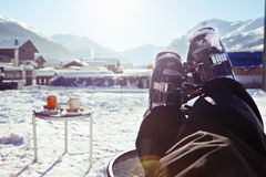 Foot of a skier wearing ski boots, sitting and having rest in a cafe. At the sun in front of winter mountains and village panorama Royalty Free Stock Photos