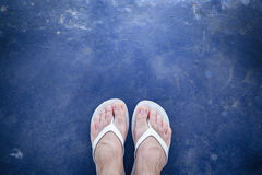 Foot and slipper on blue grunge background royalty free stock images