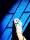 Foot slipper stepping on blue mat sad face shadow. Foot slipper stepping on mat royalty free stock photography