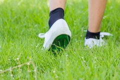 Foot in sneaker walking on grassland Stock Images
