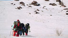 At the foot of snow hill is a group of experienced climbers, they want to climb up and over the top stock video footage