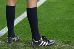 Foot of soccer referee on green grass Stock Image