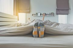 Foot with sock and feet on the bed after waking up. In morning royalty free stock image