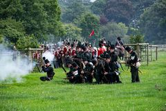 Foot soldiers firing muskets during a re-enactment. stock images