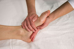 Foot sole massage. Closeup of a foot of a natural mature woman having a massage at the sole of her foot Royalty Free Stock Photos