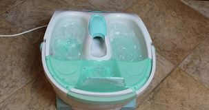 Foot spa bath with sound. Close up of home spa whirlpool foot bath with sound on bathroom tile floor stock video footage