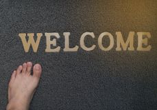 Foot stand on grey welcome mat on floor stock images