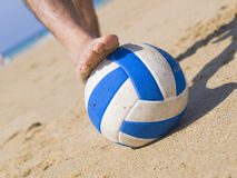 Foot stepping on a ball on the beach 2 Royalty Free Stock Photo