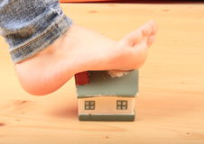 Foot stretching house. Bare foot of little girl stepping and stretching a gummy house Stock Photo