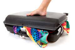 Foot on stuffed suitcase Stock Photo
