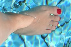 Foot in the swimming pool stock photo