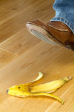 Foot about to tread on a banana skin Royalty Free Stock Images