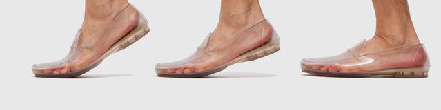 Foot in transparent shoe walking sequence. Foot in transparent plastic shoe walking sequence Royalty Free Stock Image