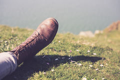 Foot wearing a boot by the sea Stock Image